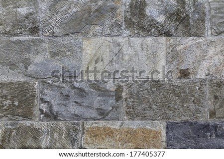 Grey tiled stone wall, construction material - stock photo