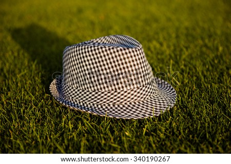Grey unisex striped hat on the grass - stock photo