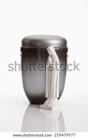 Grey urn and saint figure on white background - stock photo