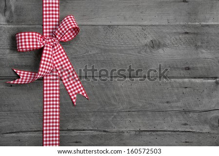 Grey wooden background with red and white checkered bow as border - stock photo