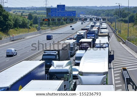 Gridlocked traffic queues after an accident on four lane motorway with warning signs on opposite carriageway - stock photo