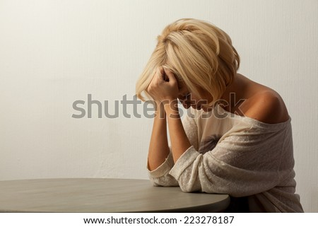 grieving beautiful woman sitting at the table - stock photo