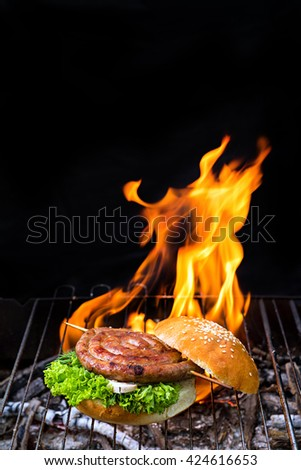 Grill concept.  Burger with salad and grilled sausage on bbq - stock photo
