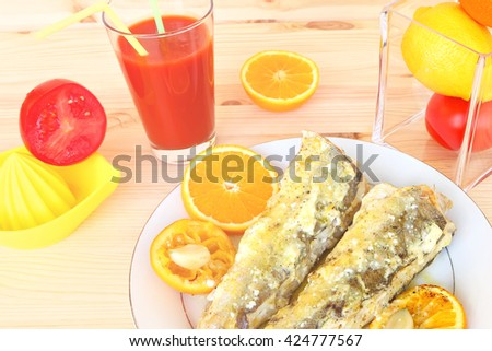 Grill fish ( Merluccius fish) with sour cream, olive oil and orange fruit with garlic and orange juice. Meal serving with tomato fresh on the wood. Mediterranean cuisine.  Toned colors vintage image - stock photo