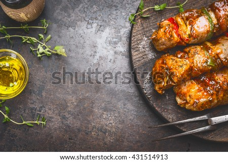 Grill food background with marinated skewers, meat fork, herbs spices and oil on dark rust metal background, top view, place for text, horizontal - stock photo