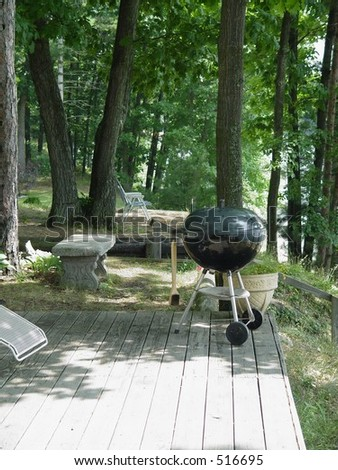 Grill on shady lake cottage deck - stock photo