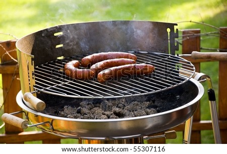 Grill sausages due to garden party. - stock photo