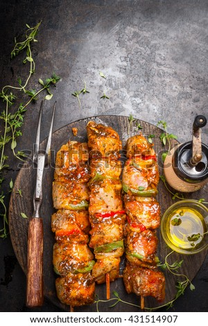 Grill time with marinated skewers, meat fork, herbs spices and oil on dark rust metal background, top view, place for text - stock photo