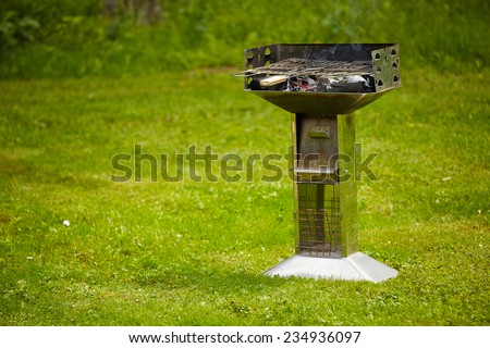 grill with burning charcoal on grass lane - stock photo