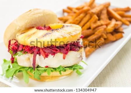 Grilled ahi tuna on arugula, topped with carrot, beet, jicama slaw and grilled pineapple on sweet Hawaiian bread bun - stock photo