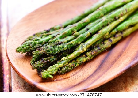 Grilled asparagus on wood platter seasoned with salt, pepper & olive oil in soft window light - stock photo
