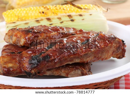 Grilled barbecue spareribs and ear of corn on a plate - stock photo