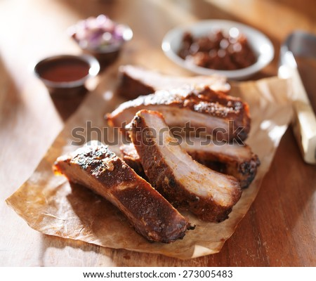 grilled barbecued spare ribs with baked beans and coleslaw  on wooden cutting board - stock photo