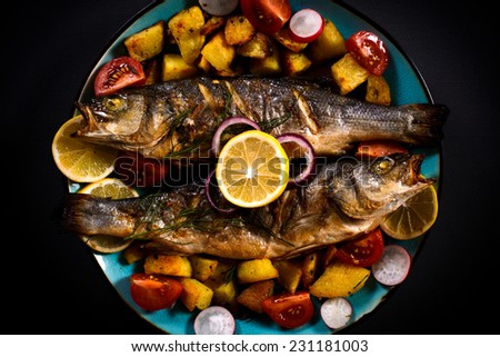 Grilled bass fish and baked potatoes in the plate,selective focus  - stock photo