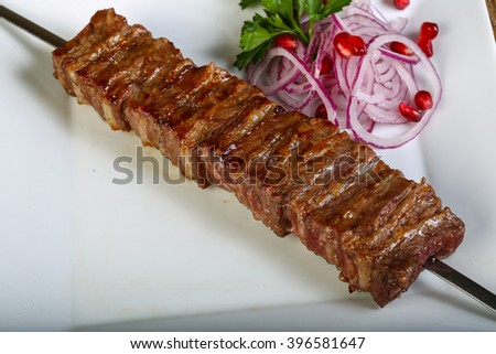 Grilled bbq ribs with onion, parsley and pomegranet seeds - stock photo