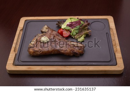 Grilled BBQ t-bone steak with fresh vegetables on stone board on wooden plate - stock photo