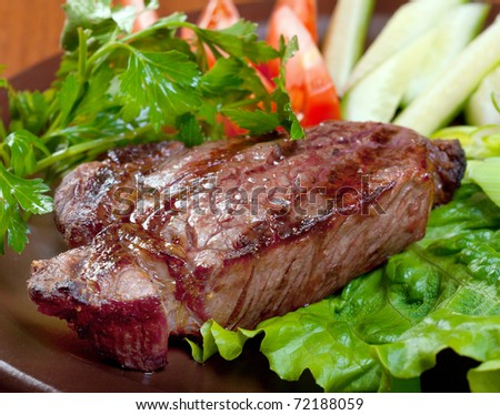Grilled beef on white plate  with vegetable.closeup - stock photo