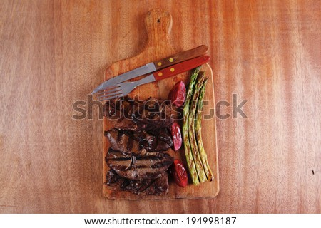 grilled beef pork meat steak fillet with asparagus  hot red peppers and cutlery on wooden cutting plate over wooden table - stock photo