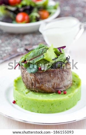 Grilled beef steak, green mashed potatoes with peas, herbs, beautiful presentation, tasty dish - stock photo