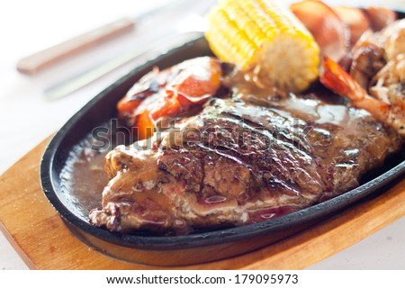Grilled beef steak served on a hot sizzling plate with sweet corn, tomatoes, big prawns and brown sauce. - stock photo