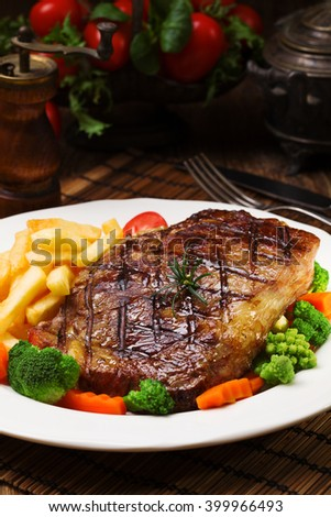Grilled beef steak served with French fries and vegetables on a white plate. - stock photo