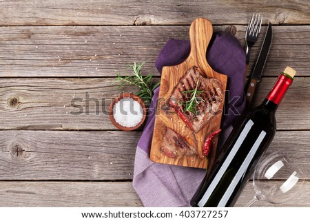 Grilled beef steak with rosemary, salt and pepper and red wine on wooden table. Top view with copy space - stock photo