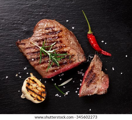 Grilled beef steak with rosemary, salt and pepper on black stone plate. Top view - stock photo