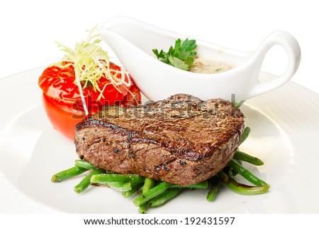 Grilled beef steak with vegetable garnish. Hearty steak dinner. - stock photo