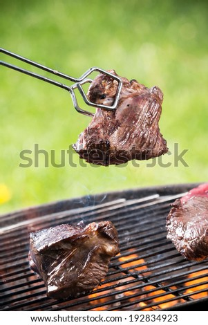 Grilled beef steaks on the grill, close-up. - stock photo