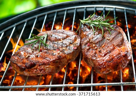 Grilled beef steaks over the coals on a barbecue grill - stock photo