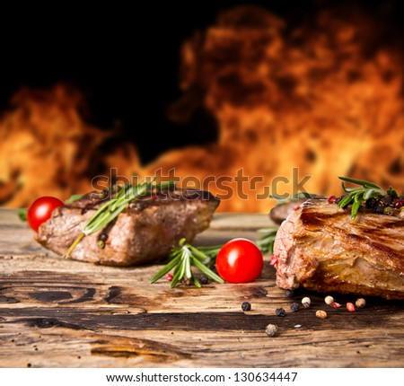 Grilled beef steaks with flames on background - stock photo