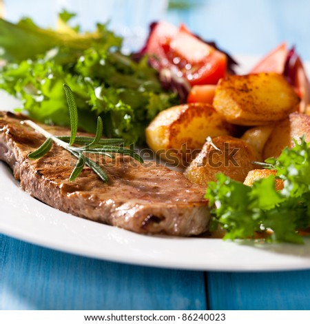 Grilled beefsteak with baked potatoes and salad - stock photo