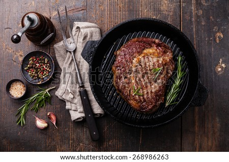 Grilled Black Angus Steak on grill iron pan on wooden background - stock photo
