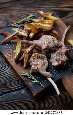 Grilled bobby veal rack steaks with fried potato, studio shot, selective focus - stock photo