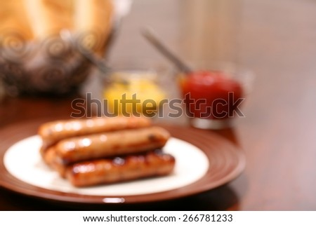 Grilled brats on a stacked on a plate ready to serve with condiments ketchup and mustard and buns ready - stock photo