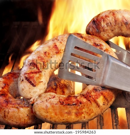Grilled bratwursts and BBQ Grate with flames in background - stock photo