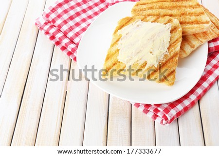 Grilled bread with butter on wooden table - stock photo