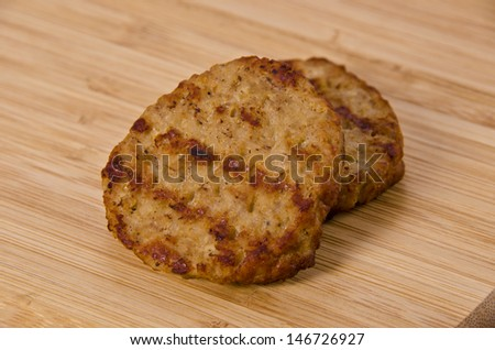 Grilled breakfast sausages isolated on a  wooden plank. - stock photo
