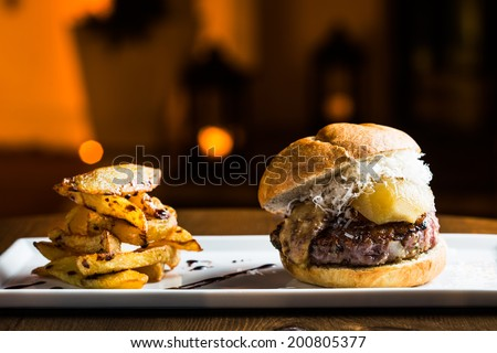 Grilled burger with foie grass, pear, cheese and fries. - stock photo
