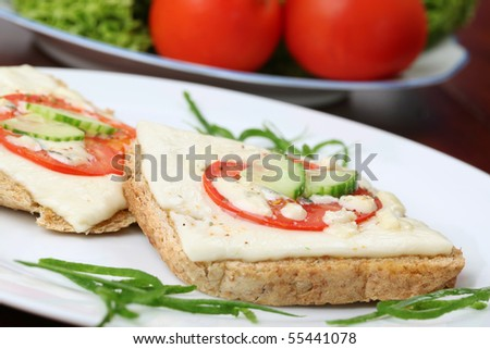 Grilled cheese and tomato sandwiches garnished with fresh cucumber ...