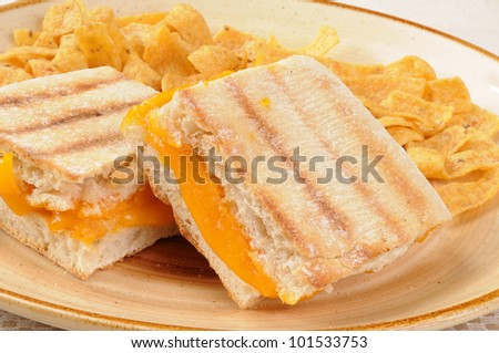 Grilled cheese panini and corn chips - stock photo