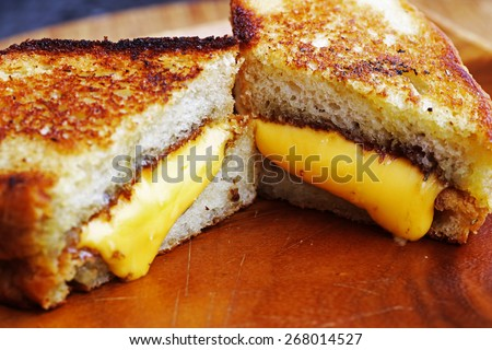 Grilled cheese sandwich made with cheddar and thick rosemary bread on wood serving platter - stock photo