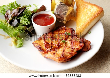 Grilled chicken, baked potatoes and chili sauce - stock photo
