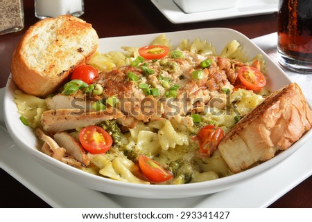 Grilled chicken breast on bowtie pasta in a creamy white wine sauce - stock photo