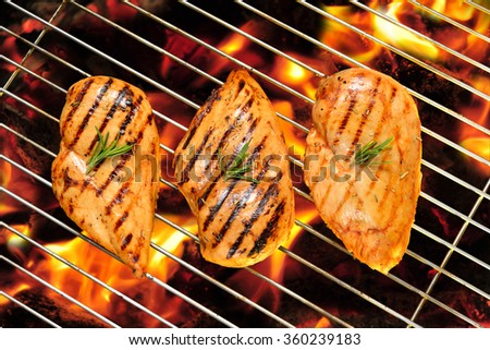 Grilled chicken breast on the flaming grill - stock photo