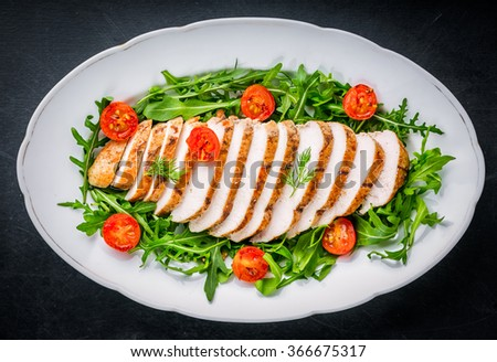 Grilled chicken breast served on lettuce with cherry tomatoes - stock photo