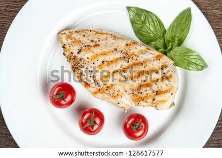 Grilled chicken breast with fresh cherry tomatoes - stock photo
