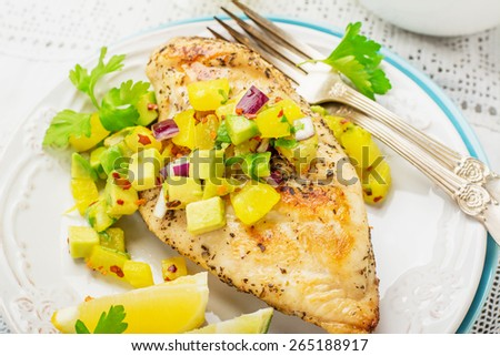 Grilled chicken breast with fresh salsa frompineapple and avocado with red sweet onion , soft selective  focus - stock photo