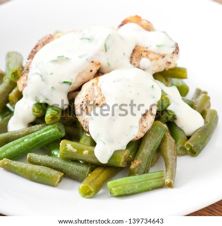 Grilled chicken breast with green beans and sauce on a white plate. - stock photo