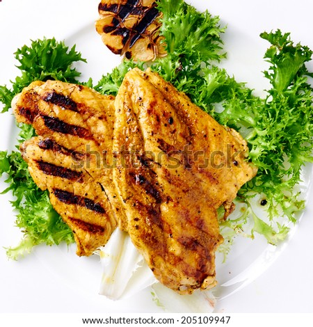 Grilled chicken breast with grilled garlic and lettuce on white plate close-up - stock photo